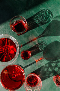 Creative beverage photography of red cocktail in different glasses under hard light over green background
