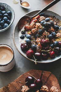 Healthy vegetarian breakfast with quinoa granola coconut bowl and coffee
