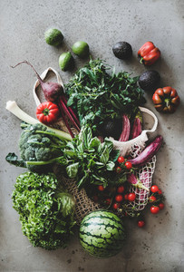 Fresh vegetables greens and fruits over grey concrete kitchen counter