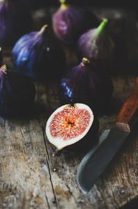 Fresh seasonal purple figs over wooden board