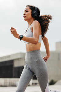 Athletic woman running through the city