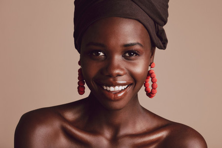 Beautiful african woman with turban against beige background