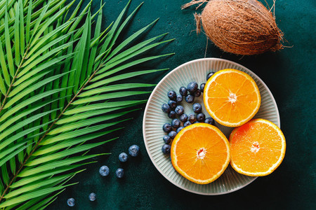 Summer flat lay with palm leaf  oranges and coconut over dark green background
