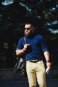bearded man walks through the city