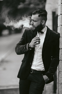 A rich man with a beard smokes electronic cigarette