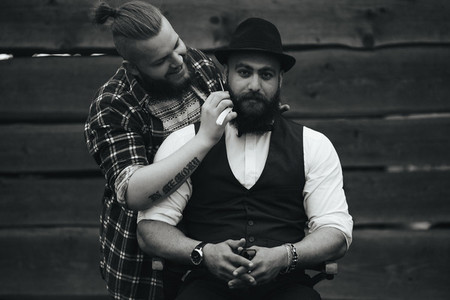 barber shaves a bearded man in vintage atmosphere