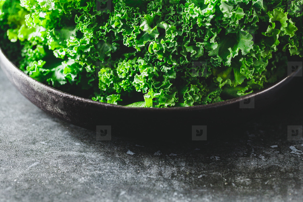 Fresh curly kale salad in a black plate over dark rustic background