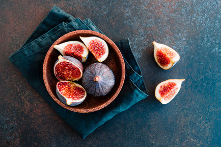 Top view of ripe figs in a wooden bowl over dark blue background