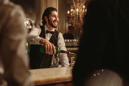 Bartender serving drink to guest at bar