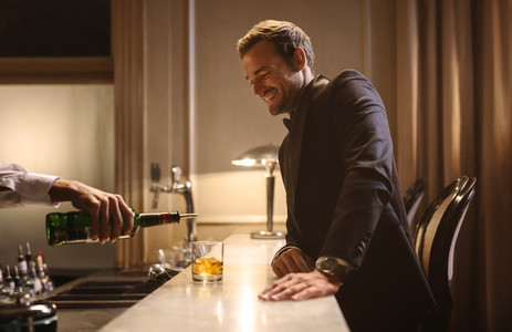 Bartender serving drink to a man at nightclub