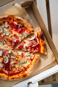 Top view of pizza with prosciutto and champignons in a delivery box