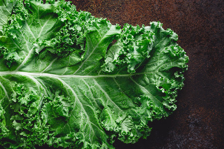 Fresh curly kale salad over dark rustic background Top view healthy eating background