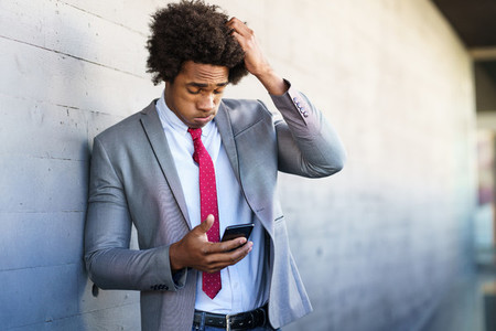 Worried Black Businessman using his smartphone outdoors