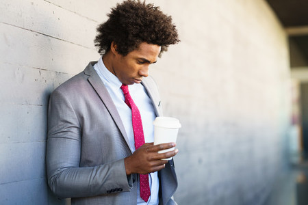 Worried Black Businessman taking a coffee break outdoors