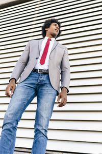 Black Businessman wearing suit walking in urban background