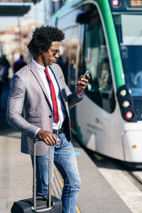 Black Businessman wearing suit waiting his train