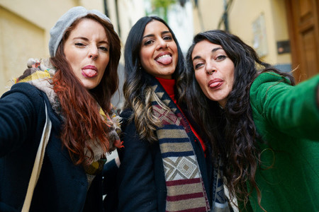 Group of woman taking a selfie photo sticking out their tongues