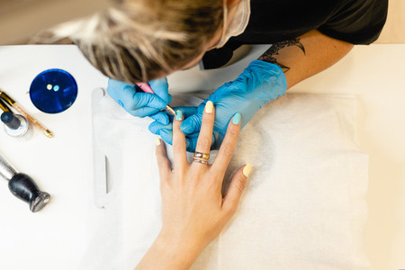 Close up of Beautician painting her clients nails in blue and yellow nail varnish