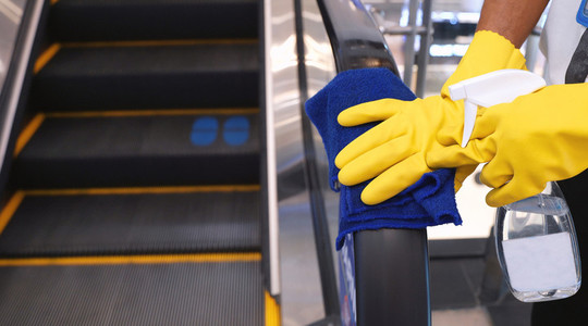 Staff cleaning the escalator hand rail in department store to pr