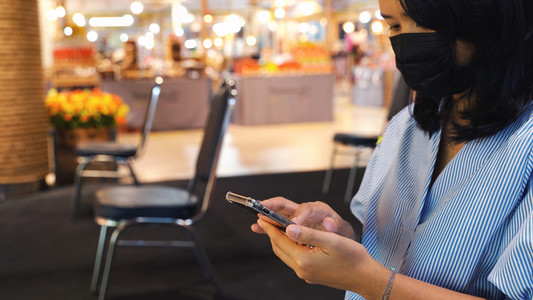 Asian woman using smartphone and sitting separated chair in shop