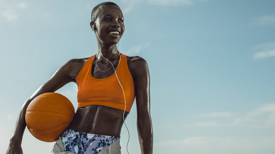 Smiling woman standing outdoors holding a basketball