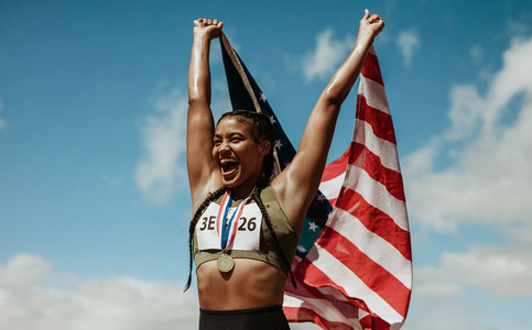 Runner celebrating victory with american flag