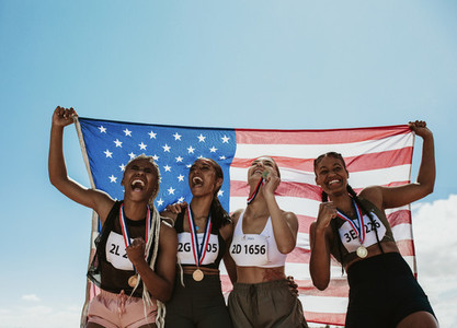 Group of winning US athletes with national flag