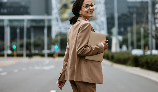 Smiling businesswoman walking on city street