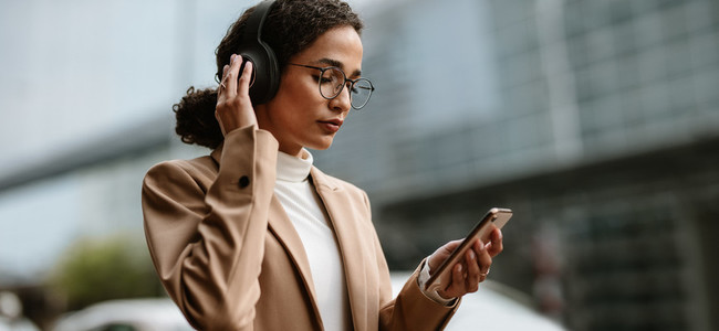 Businesswoman using truly wireless headphones while commuting