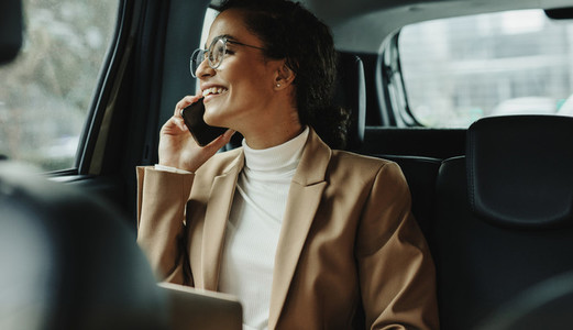 Businesswoman talking on phone while traveling by a cab