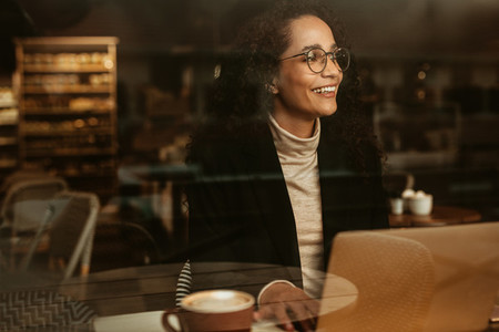 Businesswoman looking outside cafe window and smiling