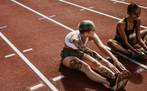 Athletes doing stretching exercises on running track