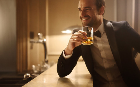 Handsome man having a whiskey at night club