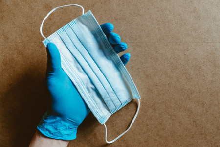 Hand in blue rubber gloves holds a medical mask  Health care and antivirus protection concept  top view