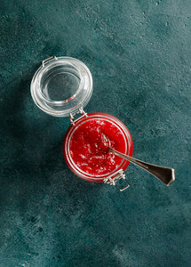 Top view of strawberry jam in a glass jar on a green background