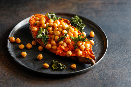 Baked sweet potato stuffed with chickpea and crunchy kale on a black plate  Vegan tasty dish for dinner or lunch