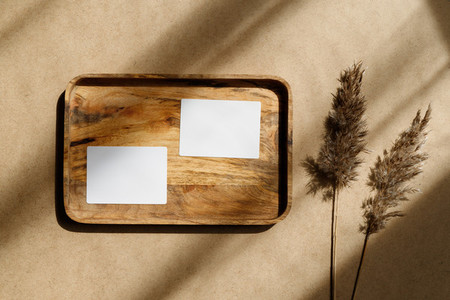 Top view of two blank paper sheet cards on a wooden tray with dry grass  Beige or sand tones  Mockup for business template  copy space