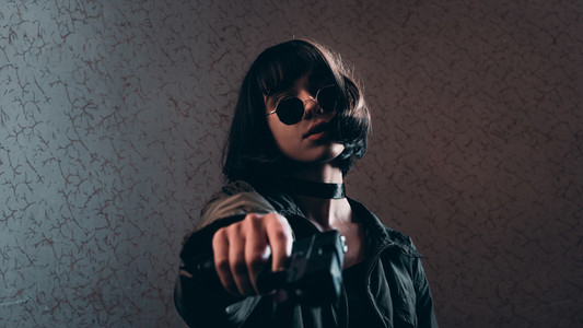 cute girl with glasses hold a gun