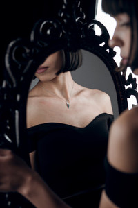 girl with silver jewelry on retro mirror background