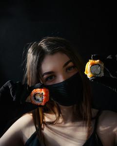 Masked girl holds sushi