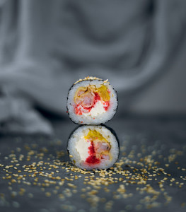 two sushi with sesame on a gray background