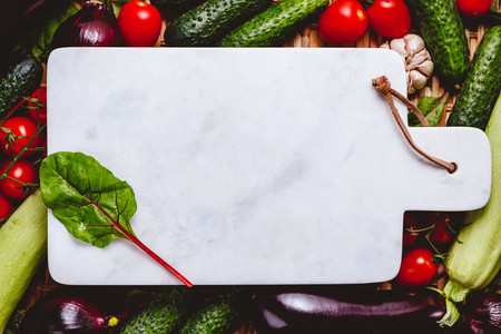 Blank white marble tray is surrounded fresh vegetables Healthy eating and cooking concept
