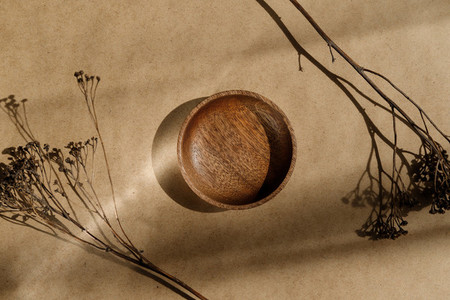 Top view of an empty wooden bowl decorated dry grass Beige or sand tones Creative composition of sunlight with shadows