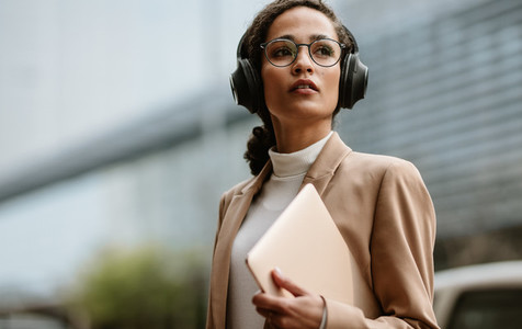 Businesswoman with headphones walking down the street