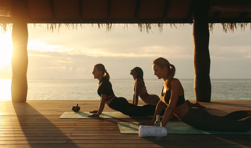 Women practicing yoga at a beach resort during sunrise