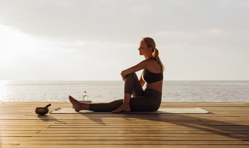 Woman practicing yoga near the sea