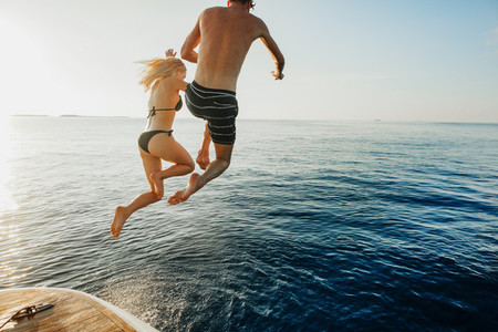 Couple jumping in to the sea from a yacht