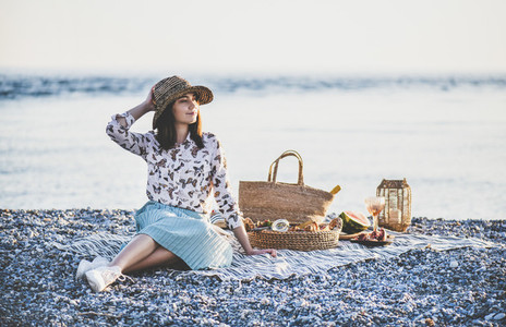 Young smiling woman having weekend picnic at seaside
