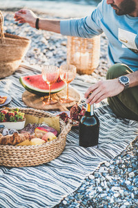 Couple having picnic with bottle of sparlking wine and snacks