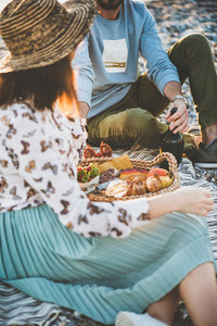 Young couple having picnic with sparkling wine  fruit and snacks